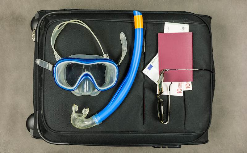 Snorkeling Gear on a travel bag near a passport